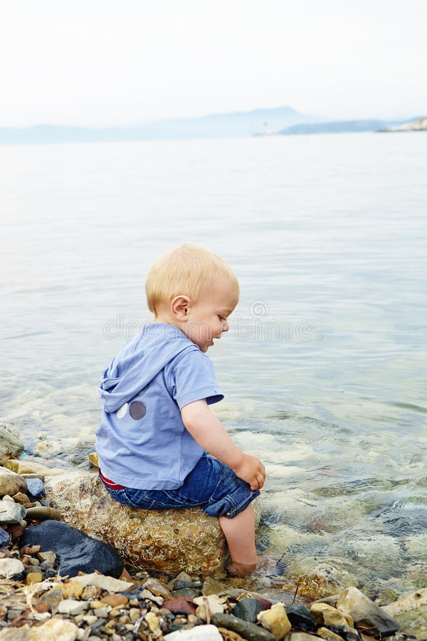 Un garçon peu blond d'ans s'asseyant sur une roche image libre de droits