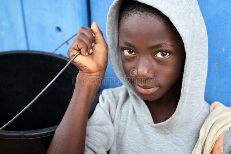 Un garçon porte un seau d'eau dans un taudis à Accra, Ghana photos stock