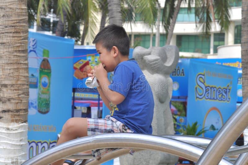 Un garçon prend le petit déjeuner dans le parc image stock