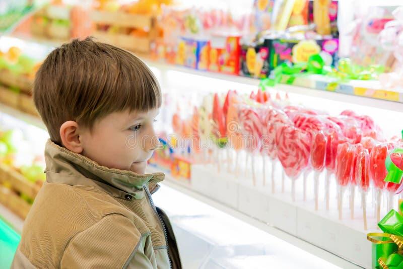 Un garçon regarde des bonbons et des bonbons sur une fenêtre de magasin à un centre commercial photo libre de droits