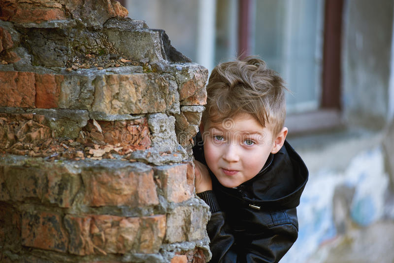 Un garçon regarde par derrière un coin, se cachant et observant image stock