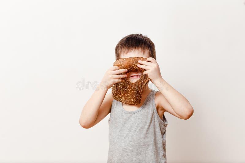 Un garçon russe de cinq ans dans un peu gris de T-shirt outre d'une crêpe d'huile Maslenitsa photo stock