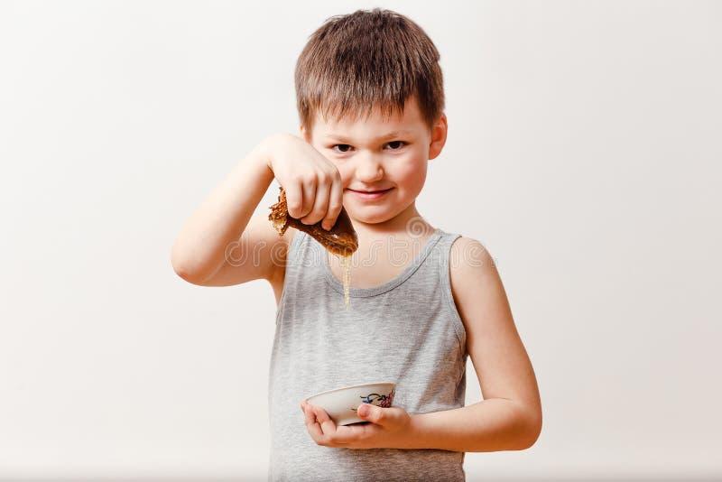 Un garçon russe de cinq ans plonge une crêpe roulée dans le miel liquide sur un fond blanc Vacances russes de Maslenitsa image libre de droits