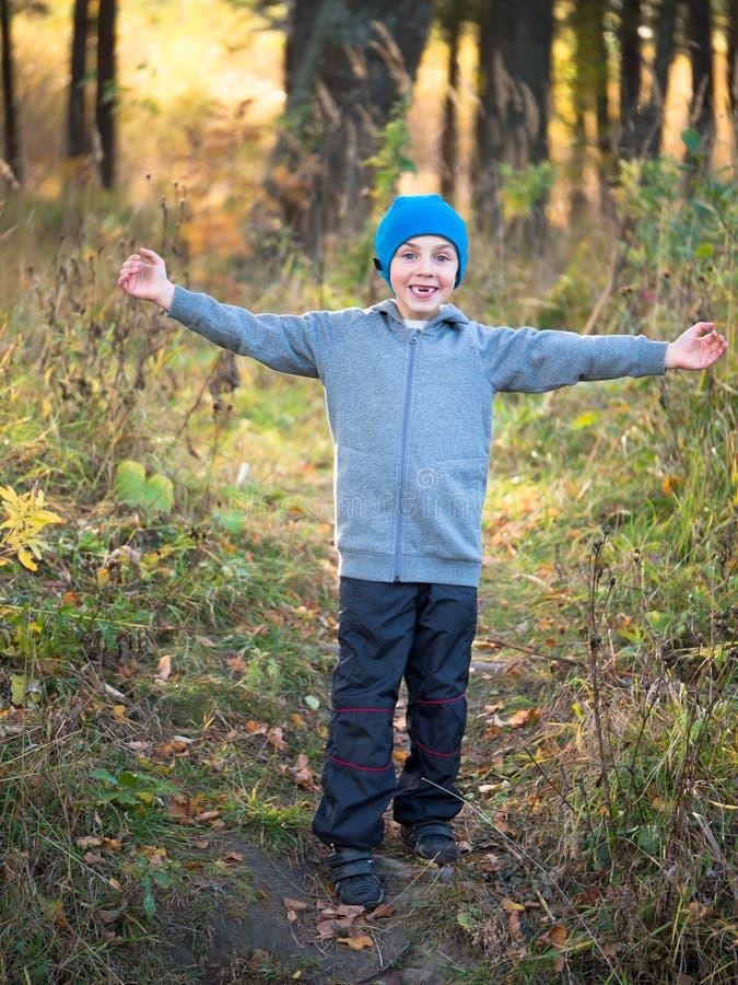 Un garçon se tient dans la clairière arme tendu et sourire images stock
