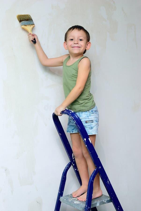 Un garçon se tient sur une échelle avec une brosse dans sa main image stock