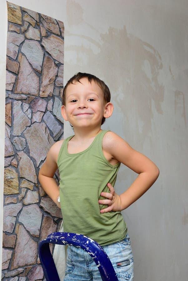 Un garçon se tient sur une échelle et colle le papier peint photographie stock libre de droits