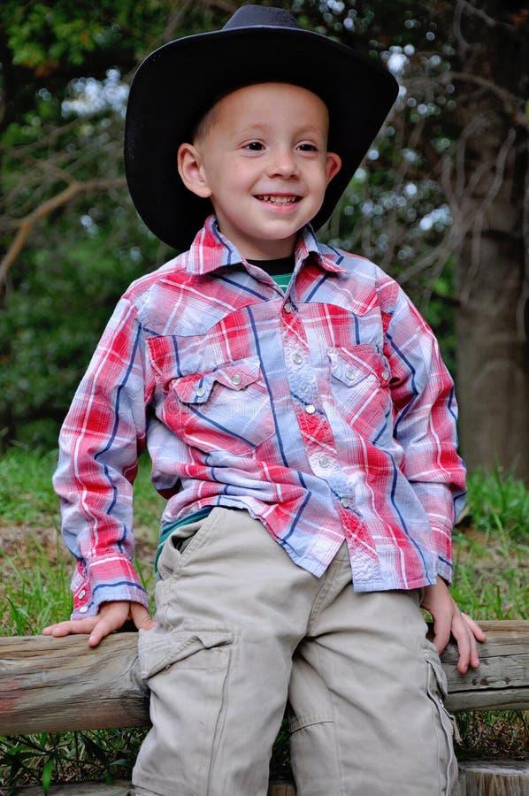 Un garçon souriant dans le style cow-boy photographie stock