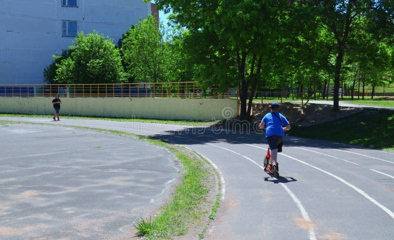 Un garçon sur un scooter rouge est le seul sur la voie image stock
