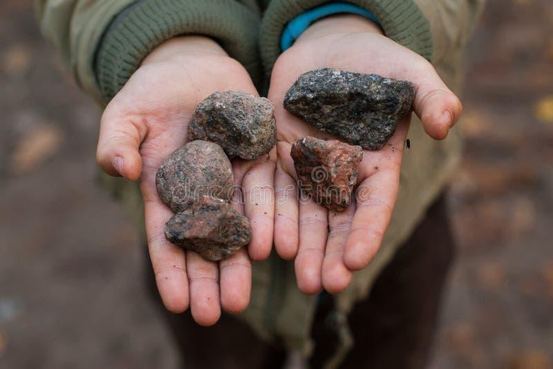 Un garçon tenant des pierres dans des ses mains photos libres de droits