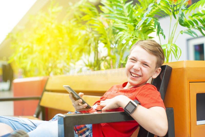 Un garçon très joyeux avec un smartphone et une horloge intelligente s'assied sur un banc et sourit Photo avec la teinture photos libres de droits