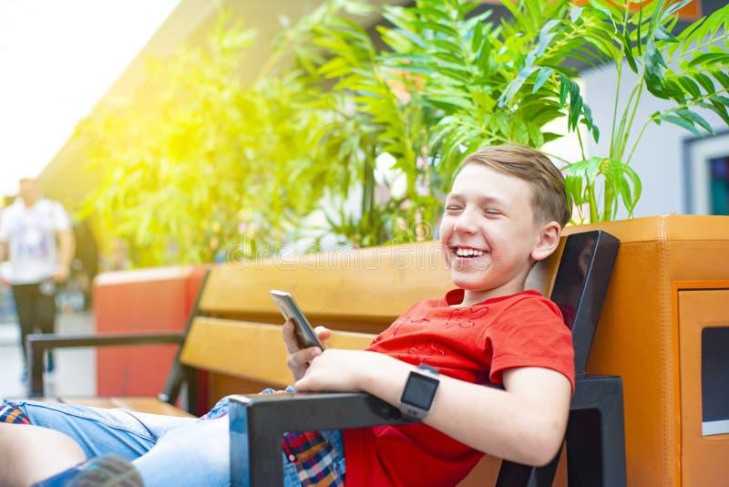 Un garçon très joyeux avec un smartphone et une horloge intelligente s'assied sur un banc et sourit Photo avec la teinture photographie stock libre de droits