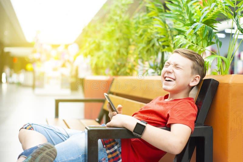 Un garçon très joyeux avec un smartphone et une horloge intelligente s'assied sur un banc et sourit Photo avec la teinture photo stock