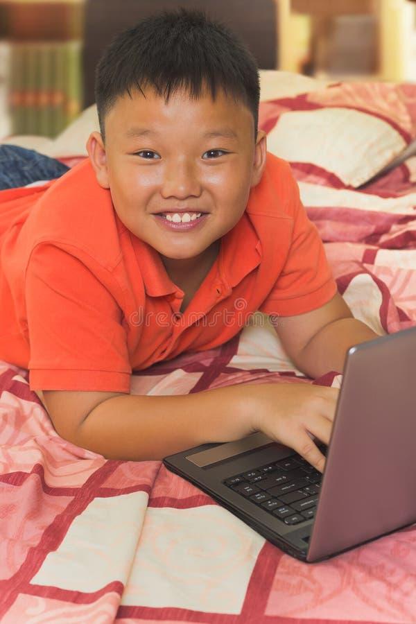 Un garçon travaillant sur un ordinateur portable image stock