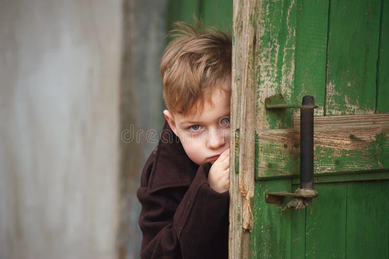 Un garçon triste regarde par derrière la porte photos libres de droits
