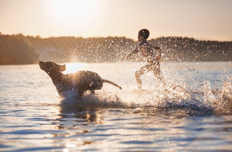 Un gar?on court avec le chien dans le lac, ?claboussant l'eau autour Moments espi?gles et heureux d'enfance Beau jour d'été de co images stock