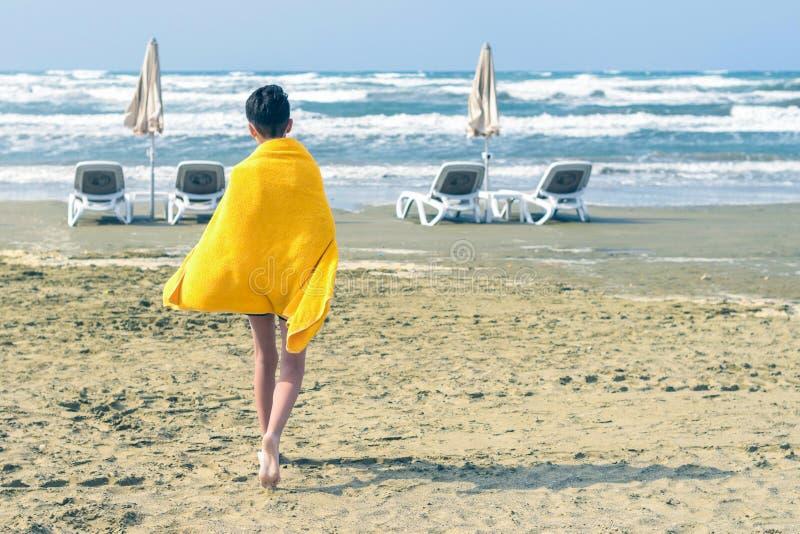 Un gar?on dans une serviette jaune marche sur la plage ar?nac?e du Mackenzie ? Larnaca par temps venteux d'automne cyprus image libre de droits
