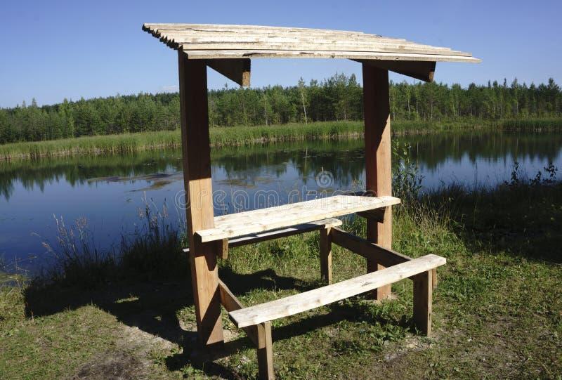 Un gazebo de madera encima mira el río adentro en un día del cielo azul fotos de archivo
