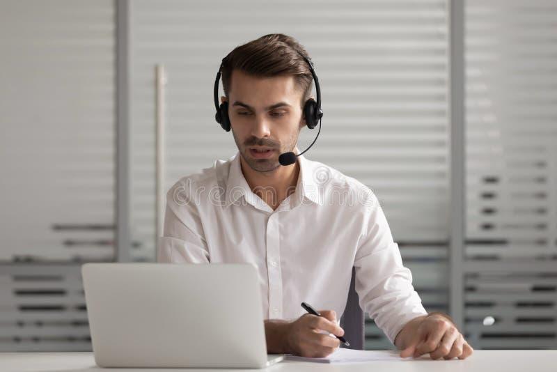 Un gestionnaire concentré et occupé, portant des casques, discutant des idées de projet avec le client photo stock