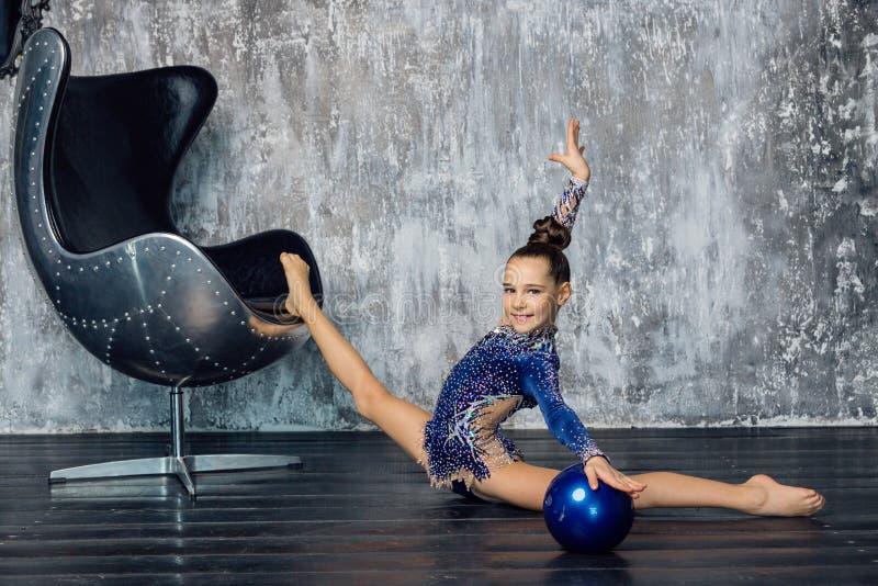 Un gimnasta de la muchacha en un traje azul para los funcionamientos se sienta en las fracturas con una pierna en la silla fotografía de archivo libre de regalías