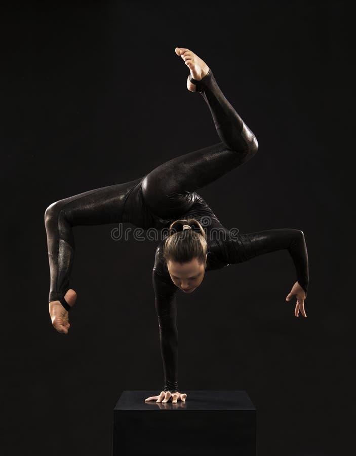 Un gimnasta encantador de la muchacha, en un traje negro, dedicado a la acrobacia teniendo en cuenta el contra imagen de archivo