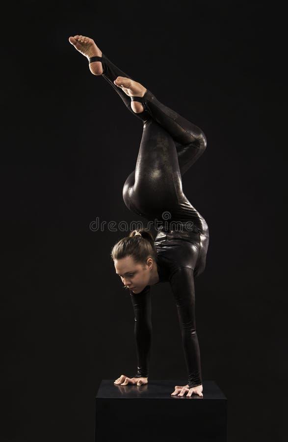 Un gimnasta encantador de la muchacha, en un traje negro, dedicado a la acrobacia teniendo en cuenta el contra foto de archivo libre de regalías