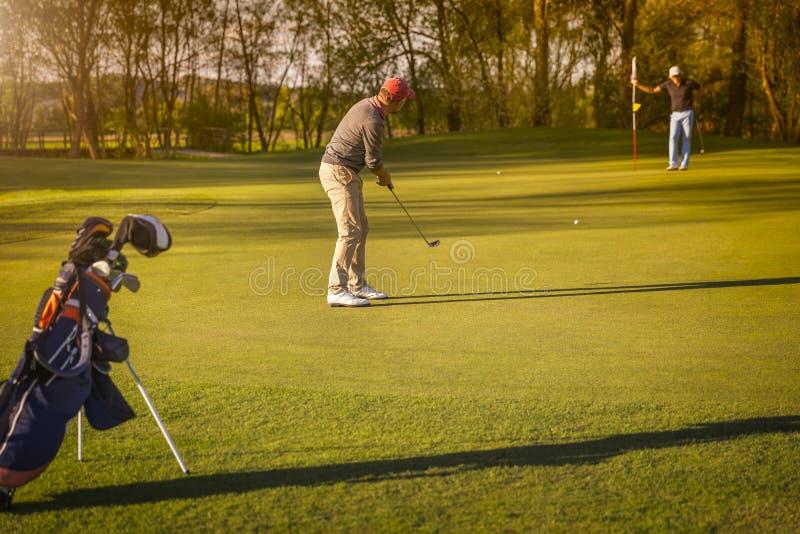 Un giocatore di golf di due anziani che gioca golf al crepuscolo immagini stock libere da diritti
