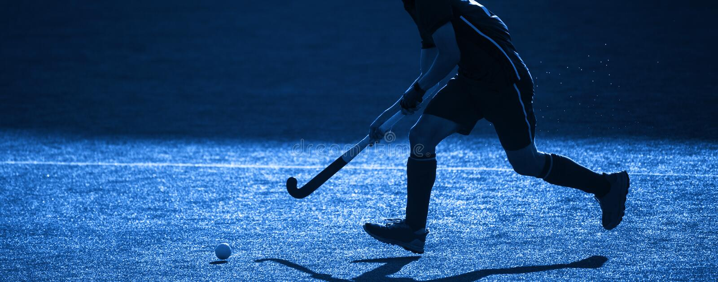 Un Giocatore Di Hockey Su Campo Sta Per Passare La Palla Filtro blu immagine stock libera da diritti