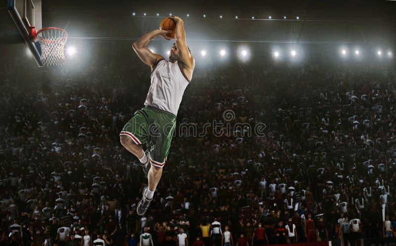 Un giocatore di pallacanestro salta nella vista di panorama dello stadio immagine stock