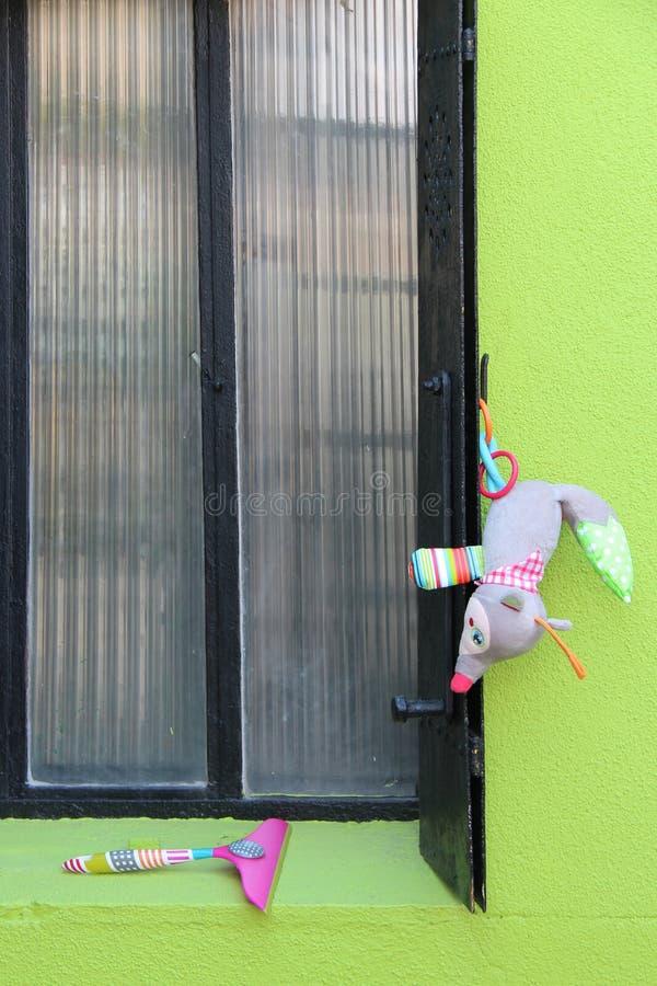 Un giocattolo è appeso su un otturatore ed altro ha messo sull'orlo di una finestra (Francia) fotografie stock