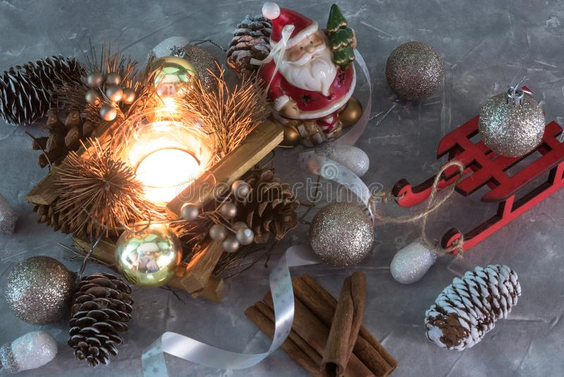Un giocattolo di Santa Claus, una candela bruciante e una slitta Feste di natale insieme degli ornamenti di Natale su calcestruzz immagini stock libere da diritti