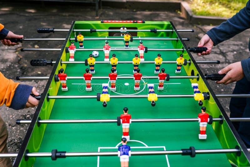 Un gioco di calcio-balilla Due persone che giocano l'esterno di calcio-balilla Spettacolo durante le feste o il tempo libero Giov fotografie stock libere da diritti