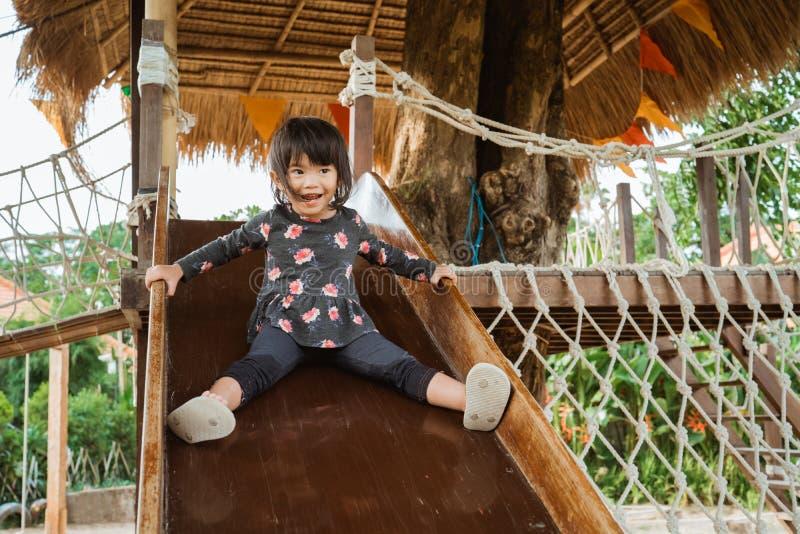 Un gioco molto felice asiatico sveglio della bambina scorrevoli in un campo da giuoco fotografia stock libera da diritti
