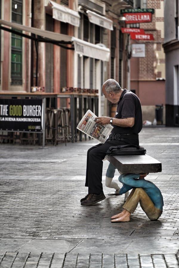 Un giornale della lettura dell'uomo su un banco a Malaga, Spagna fotografie stock