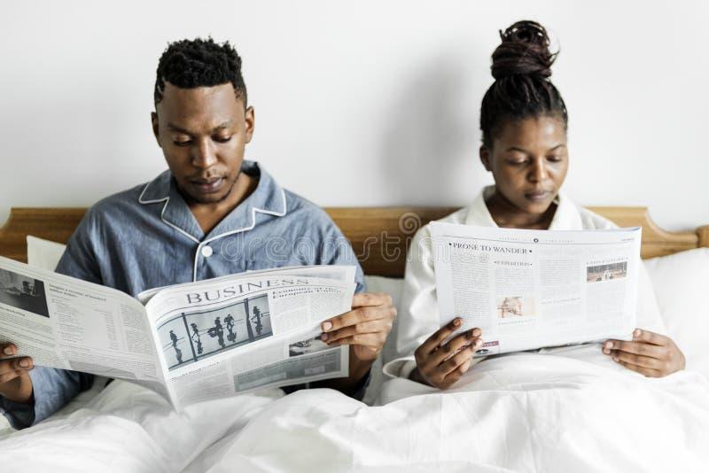 Un giornale felice della lettura delle coppie a letto immagine stock