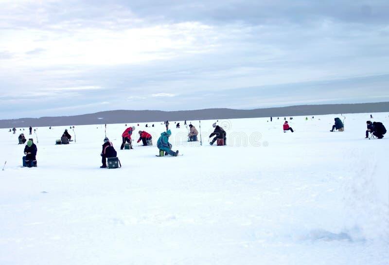 Un giorno di inverno soleggiato, ci sono pescatori che si siedono su un grande lago fotografia stock libera da diritti
