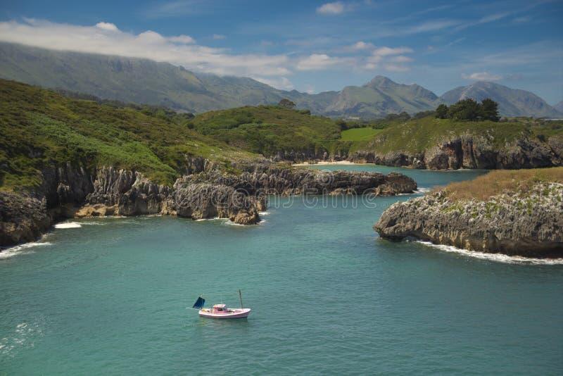 Un giorno pacifico sopra una barca vicino alla costa ed alla montagna fotografie stock