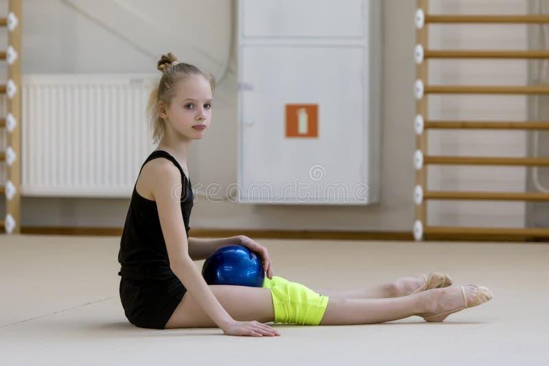 Un giovane adolescente prepara per la prestazione, scaldandosi ed esegue gli elementi relativi alla ginnastica ai concorsi immagine stock libera da diritti