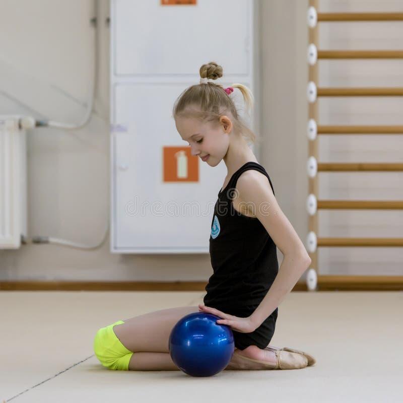 Un giovane adolescente prepara per la prestazione, scaldandosi ed esegue gli elementi relativi alla ginnastica ai concorsi immagini stock libere da diritti