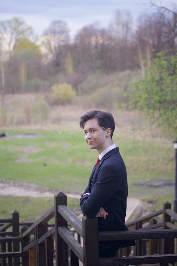 Un giovane, un adolescente, in un vestito classico Sta sulla scala di legno, le sue armi hanno ripiegato il suo petto e esamina fotografia stock