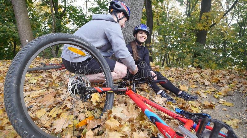 Un giovane aiuta una donna che è caduto da una bicicletta immagine stock