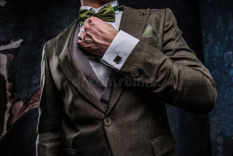 Un giovane alla moda vestito in un vestito elegante per correggere la sua cravatta a farfalla contro una parete strutturata scura immagine stock libera da diritti