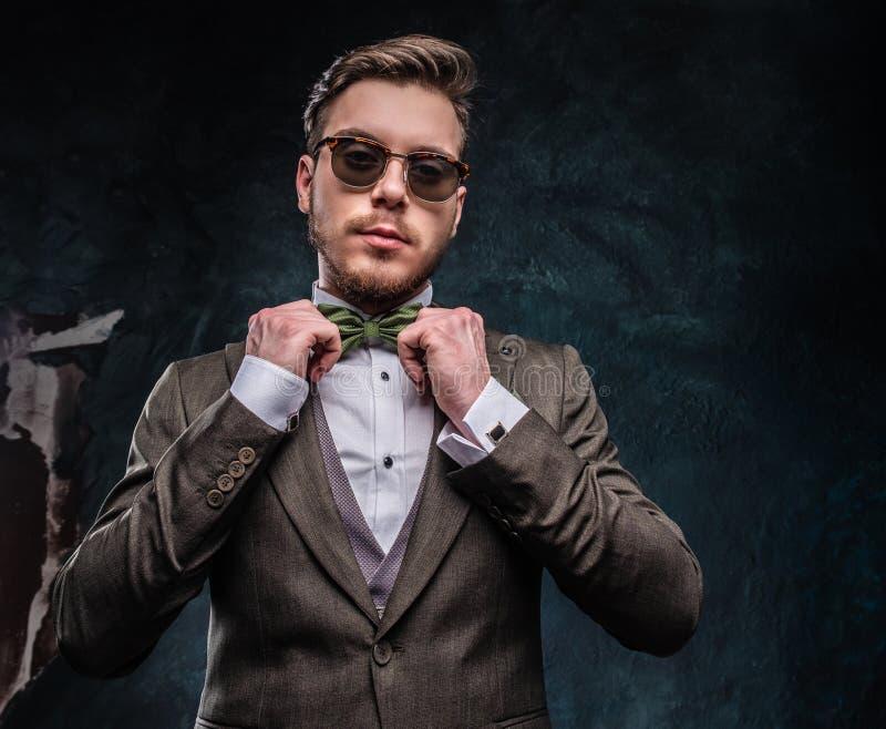 Un giovane alla moda vestito in un vestito elegante per correggere la sua cravatta a farfalla contro una parete strutturata scura fotografie stock