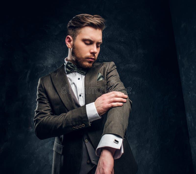 Un giovane alla moda vestito in un vestito elegante per correggere la sua manica contro una parete strutturata scura immagine stock