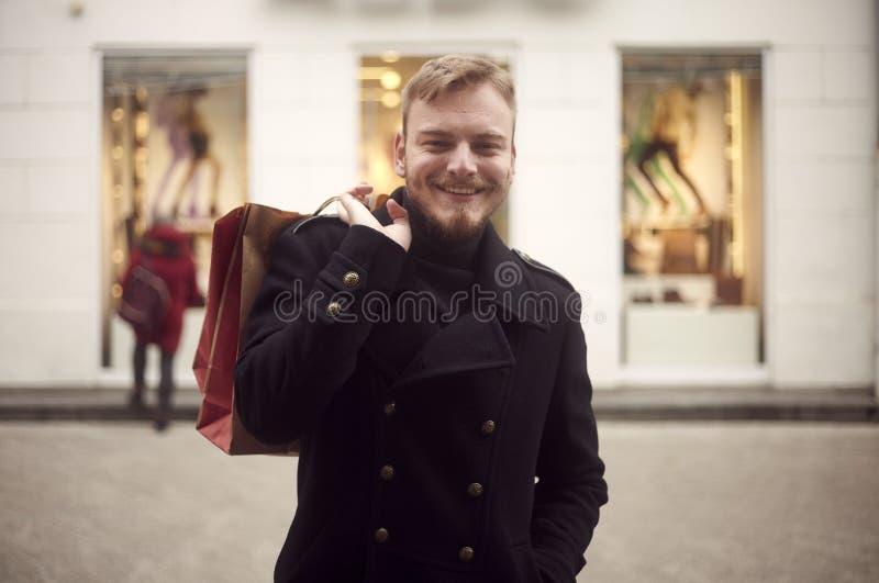 Un giovane, 20-29 anni, guardanti alla macchina fotografica nel colpo dell'ente anteriore e superiore Sorridere tenendo sacchetto immagine stock libera da diritti