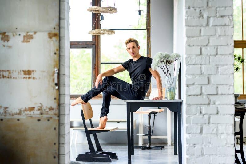 Un giovane ballerino bello che si rilassa in un appartamento di stile del sottotetto fotografia stock libera da diritti