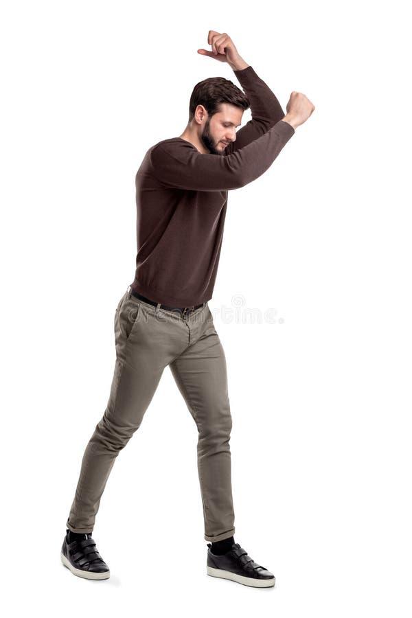 Un giovane barbuto di misura in abbigliamento casual prova a colpire o rompere qualcosa che tiene uno strumento invisibile immagini stock