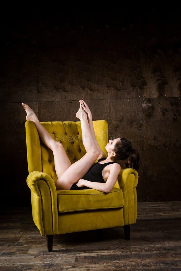Un giovane bello, donna caucasica sexy con la figura sottile e gambe nude lunghe, posanti a piedi nudi adagiarsi sulla poltrona g immagine stock libera da diritti