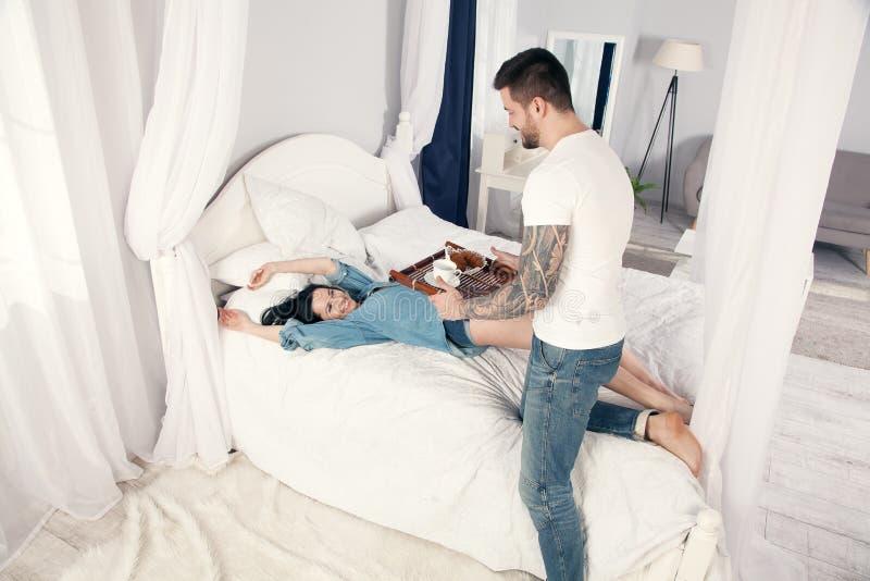 Un giovane, giovane bello ha portato i croissant ed il caffè per la prima colazione nel letto alla sua ragazza cara immagine stock libera da diritti