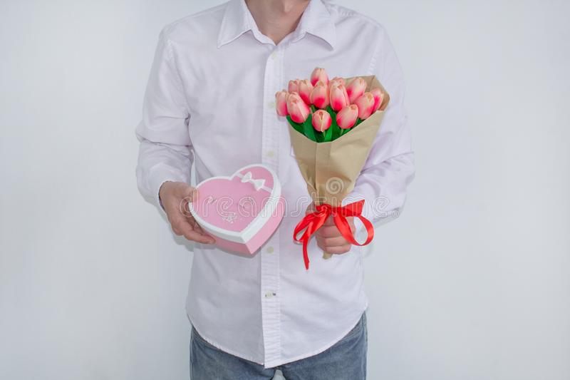 Un giovane in camicia bianca e jeans, tenendo un mazzo dei tulipani e di un contenitore di regalo in forma di cuore, su un fondo  immagine stock