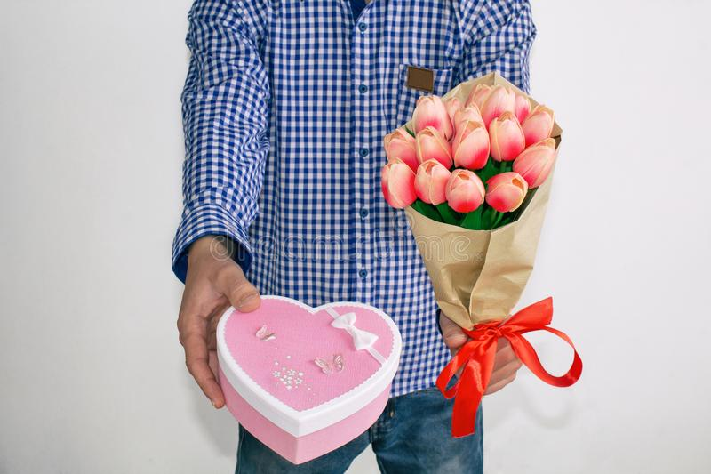 Un giovane in camicia e jeans di plaid blu, danti un mazzo dei tulipani e di un contenitore di regalo in forma di cuore, su un fo fotografia stock libera da diritti